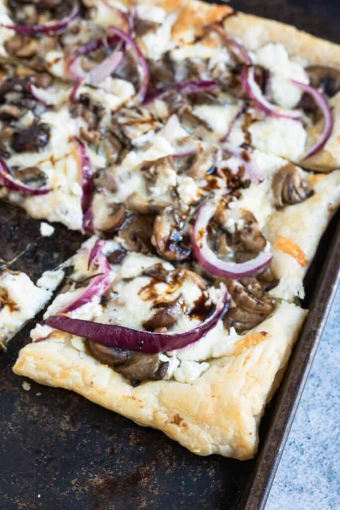 puff pastry pizza on a baking try with goat cheese and mushrooms