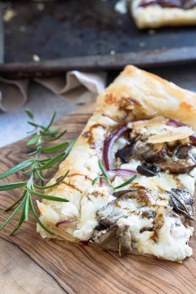 wild mushrrom and goat cheese pizza made with puff pastry on serving platter with rosemary and balsamic drizzle