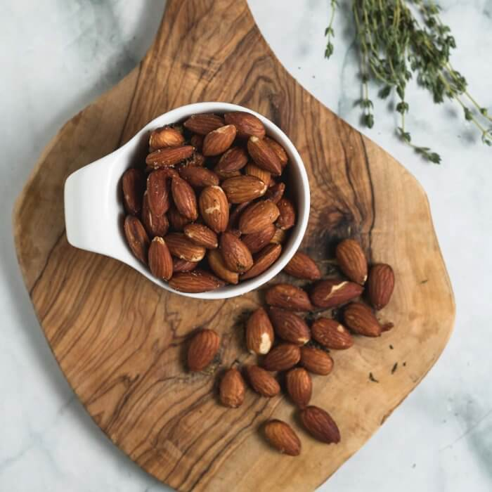 thyme and sea salt roasted almonds on a small wooden board