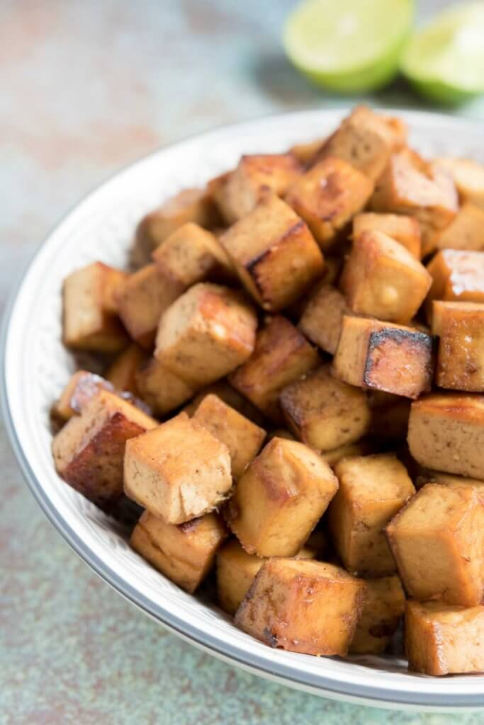 soy, lime and sesame baked tofu in a bowl with lime