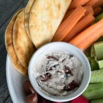 tahini and greek yogurt tip with olive on a platter with pita and fresh vegetables for dipping