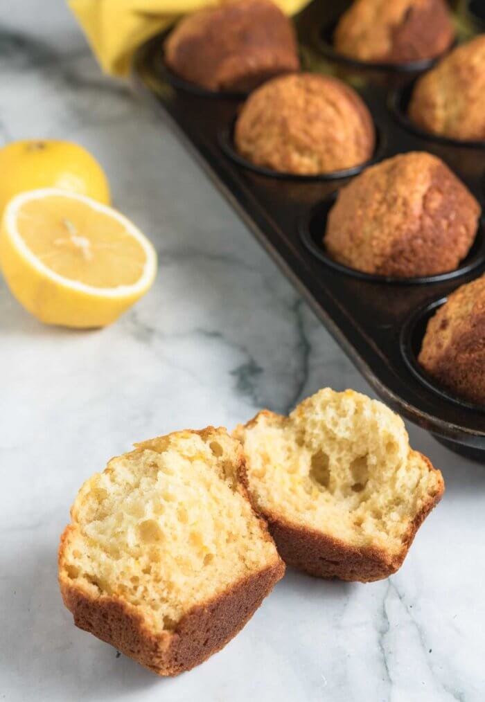 a lemon muffin broken in half next to a tray of muffins and fresh lemons