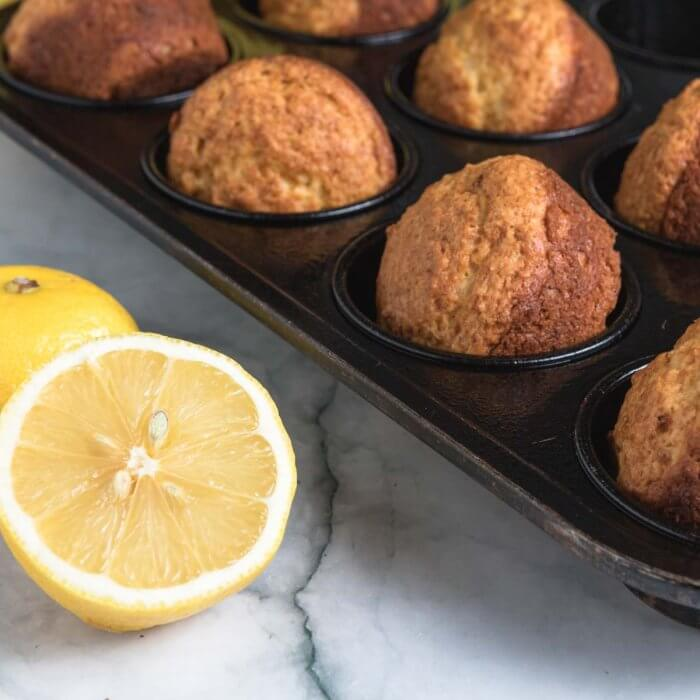 lemon muffins in a backing tray after lemon glaze has been added.
